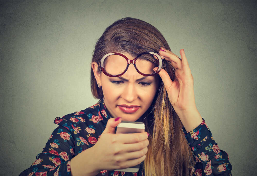 Woman squinting looking at her phone