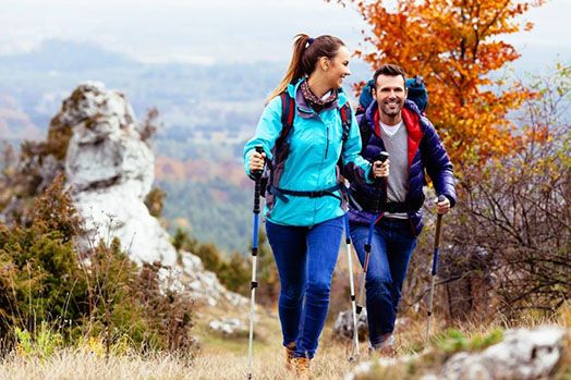 A man and a woman are hiking up a mountain side.
